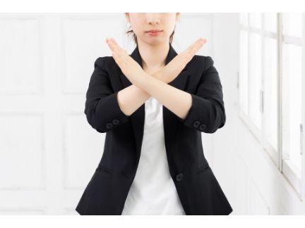 手をバツにする女性の写真
