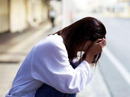 しゃがみ込んで泣く女性の写真