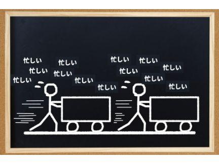台車を押す絵とその周りに「忙しい」の文字がいっぱいある写真