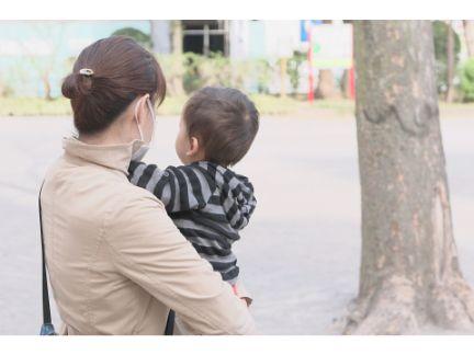 子供を抱っこする母親の後ろ姿