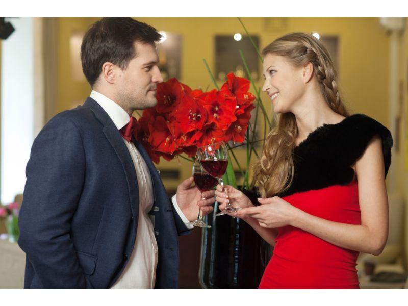 男女がワインを飲みながら会話している写真
