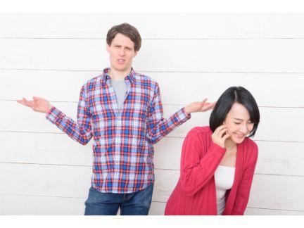 電話する女性の後ろで、両手を広げ呆れる男性の写真