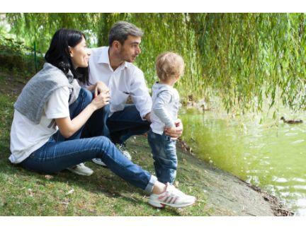 親子3人で川辺で遊んでいる写真