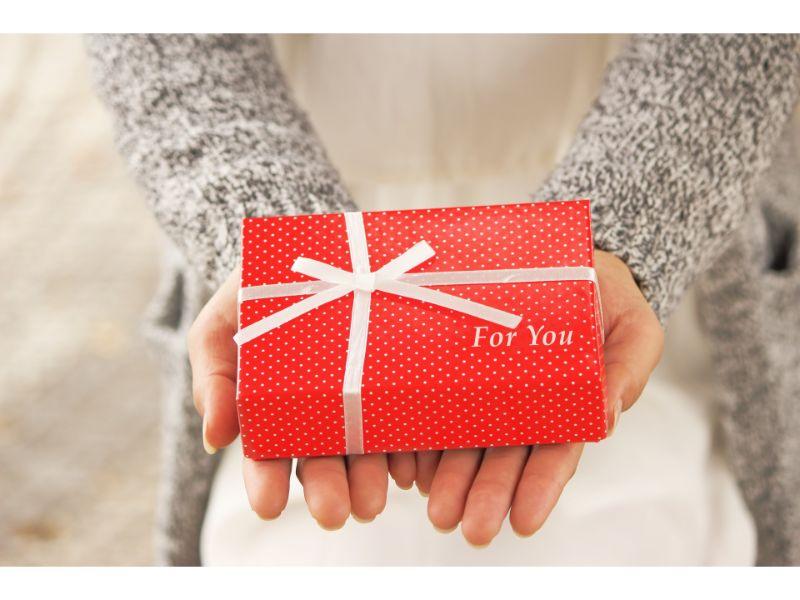 プレゼントを差し出す女性の手の写真