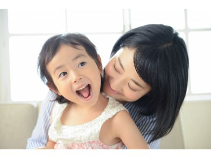 後ろから笑っている子供を抱きしめる母親の写真