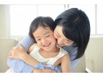 子供を後ろから抱きしめる母親の写真
