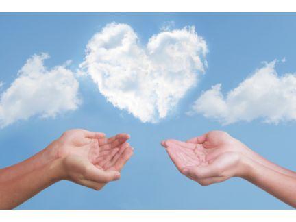 ハートマークの雲を両手で受け止めてとする男女の写真