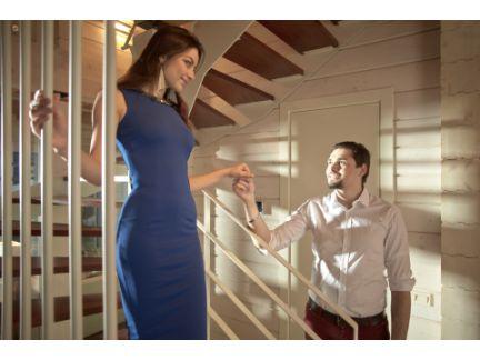 階段を降りる女性に手を差し伸べる男性の写真