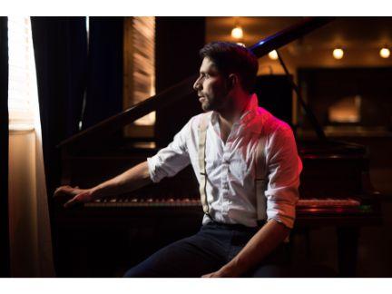 ピアノの前に座り窓の外を見つめる男性の写真
