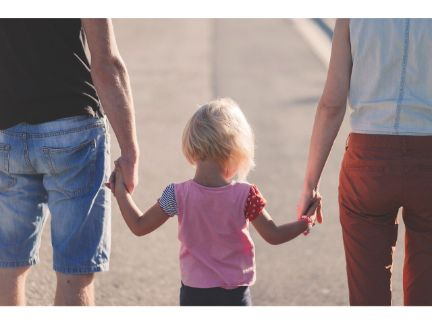 両親の間に子供を挟み3人で手を繋ぐ後ろ姿