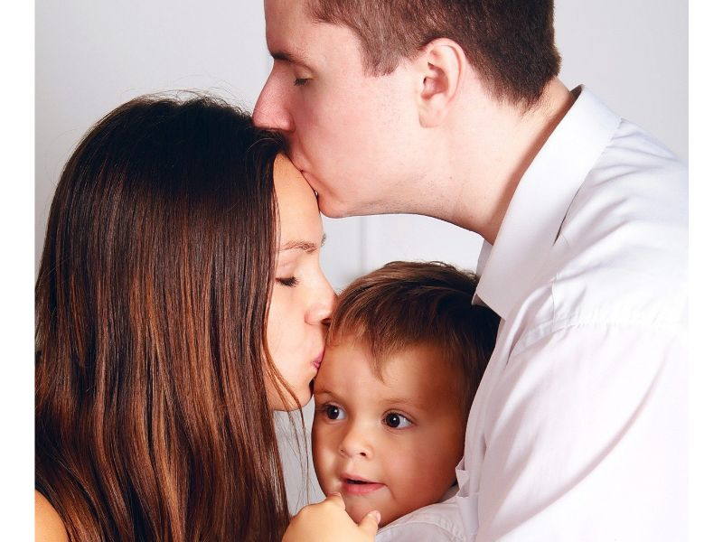 旦那が奥様のおでこにキス、奥様が夫婦の間にいる赤ちゃんのおでこにキスする写真