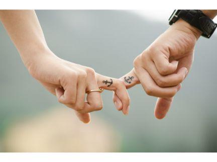 男女が指を繋いでいる手元の写真