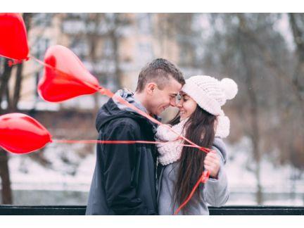 風船を持って見つめ合うカップルの写真