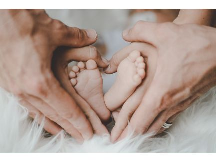 赤ちゃんの足と夫婦の手を順番に重ね、ハートマークを作る写真