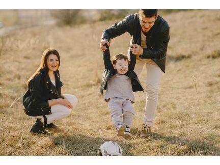 子供と遊ぶ父親とそれを笑ってみる母親の写真