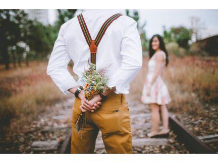 花束を後ろ手に隠して告白する男性の写真