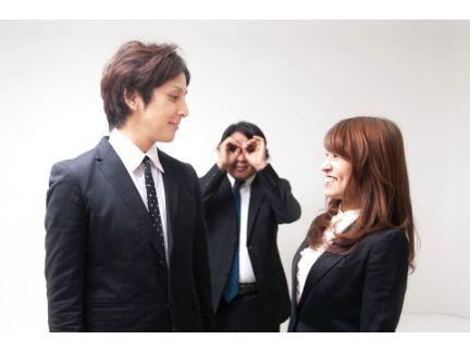 男女が楽し気に話しているのを、上司が遠くで見ている写真