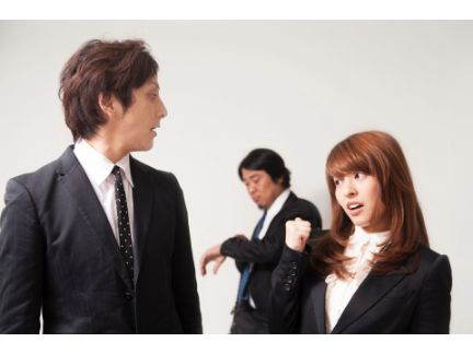 男女が遠くに離れた上司を指さしている写真