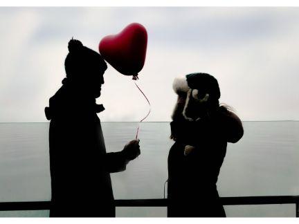 風船を持った男性が女性に告白している写真