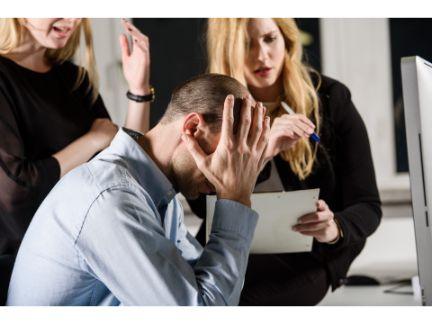 女性2人に責められ、頭を抱える男性の写真