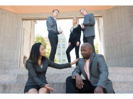 男性を慰める女性とそれを見ている同僚達の写真