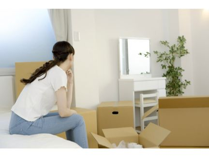 引っ越し準備をしながら悩む女性の写真
