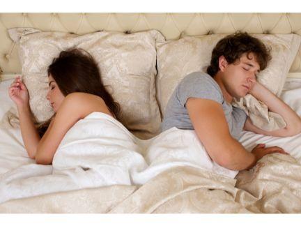 背中合わせで寝るカップルの写真