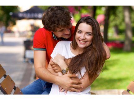 後ろから抱きしめるカップルの写真