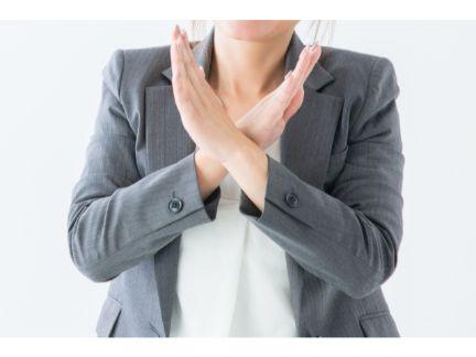 手でバツする女性の写真
