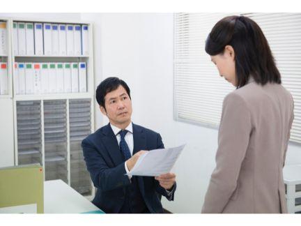 女性の部下を叱る男性上司の写真