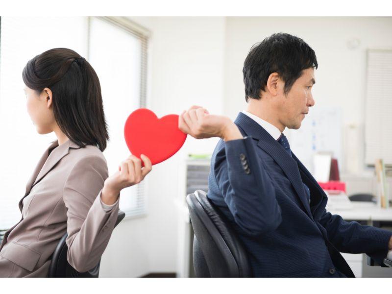 オフィスで男女が背中合わせに座りハートマークを受け渡している写真
