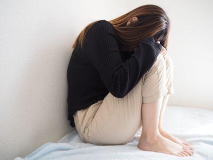 ベッドの上で膝を抱えて落ち込む女性の写真