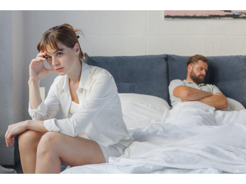 ベッドの上の男性と離れて座る女性の写真