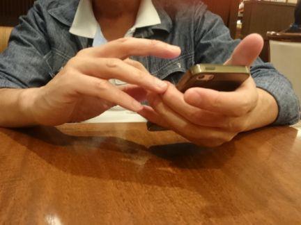 スマホを操作する男性の手の写真