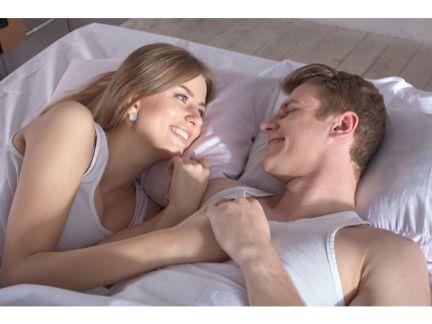 ベッドで見つめ合うカップルの写真