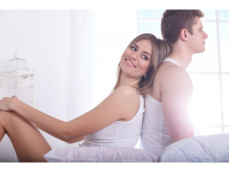 背中合わせて笑顔のカップルの写真