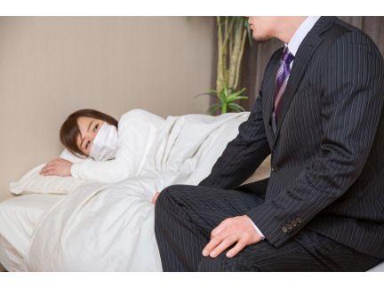 病気の女性と看病する男性の写真