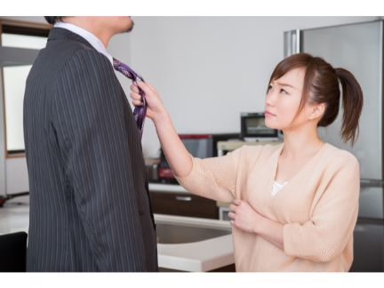 男性の首根っこを摑まえ怒る女性の写真
