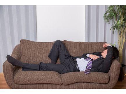 ソファーで寝るビジネスマンの写真