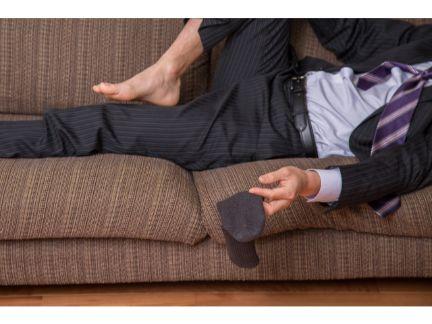 酔っぱらってソファーで寝る男性の写真