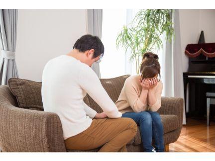 ソファーで泣くカップルの写真