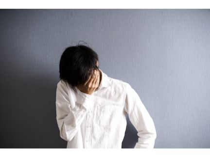 顔を覆い悲しむ男性の写真