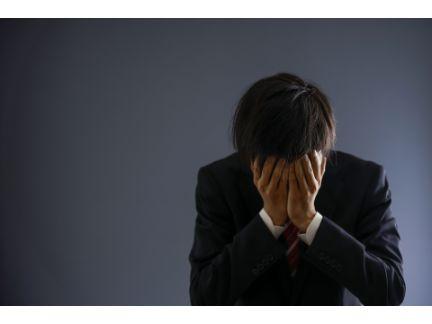 男性が顔を両手で覆い、悩んでいる写真