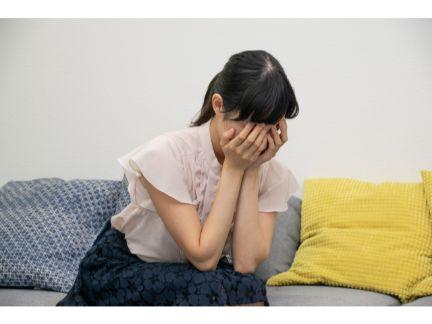 両手で顔を覆い泣く女性の写真
