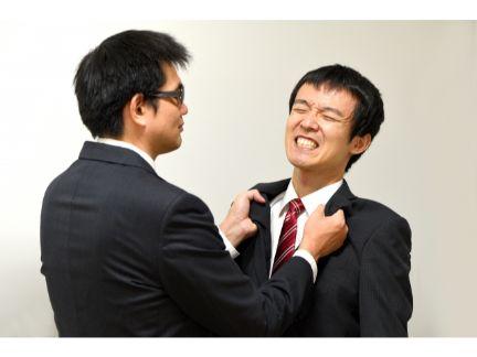 男性の襟首をつかむ上司の写真
