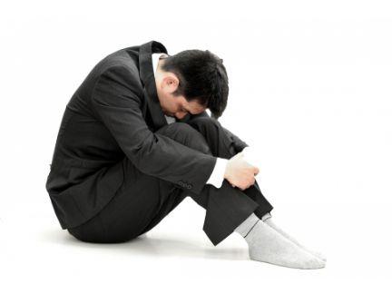 膝を抱えてうつ向く男性の写真