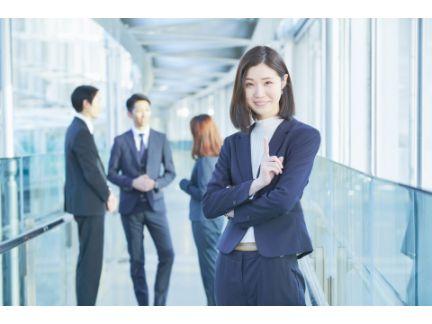 男女で話す中に入らず、1人離れて立つ女性の写真