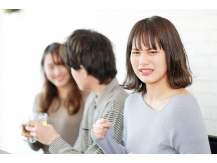 他の女性と話す男性と、その横で嫉妬する女性