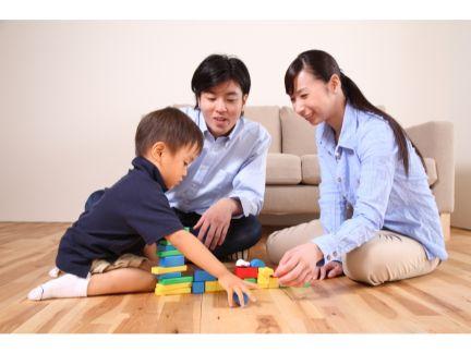 子供と遊ぶ夫婦の写真