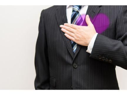 男性が胸に手を当て、ドキドキしている写真
